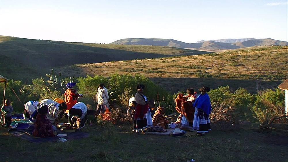 Basotho women in traditional dress, making a fire in rural Lesotho highlands, Lesotho, Africa