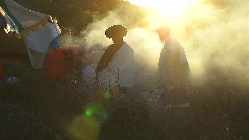 Basotho women in traditional dress, cooking on a fire in rural Lesotho highlands, smoke blowing in wind at sunset/sunrise, Lesotho, Africa