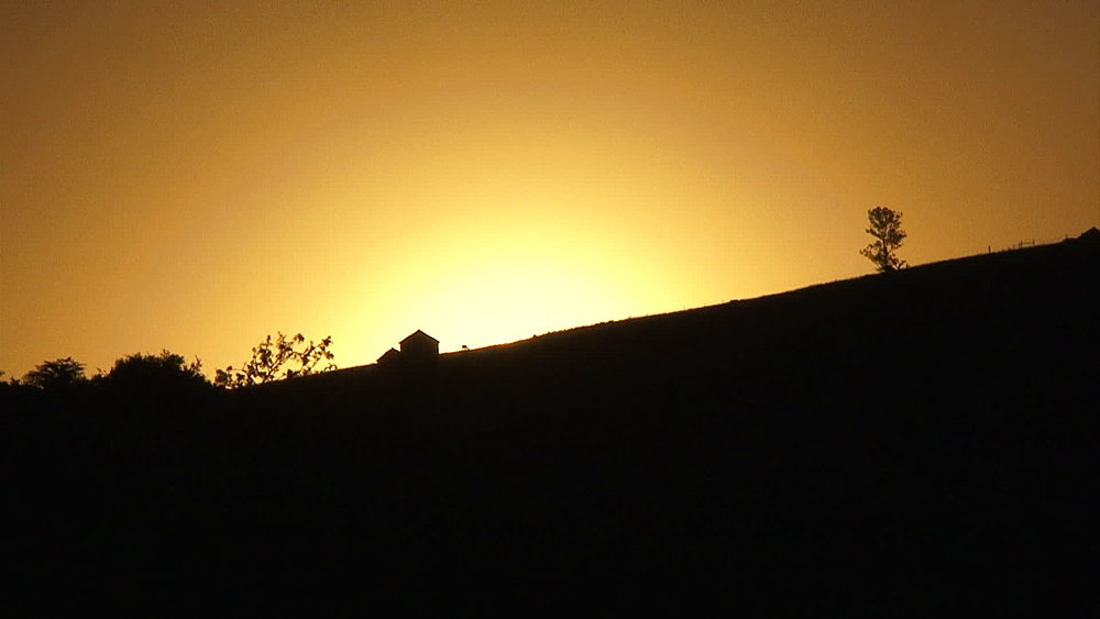 Silhouette of hut in Lesotho highlands at sunset/sunrise, dawn/dusk, Rural Lesotho, Africa