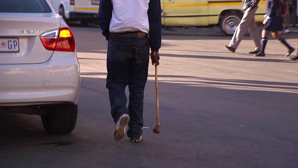 A man carrying a knobkerrie, knobkierrie, traditional weapon, walking down a busy street in downtown Johannesburg, South Africa, Africa