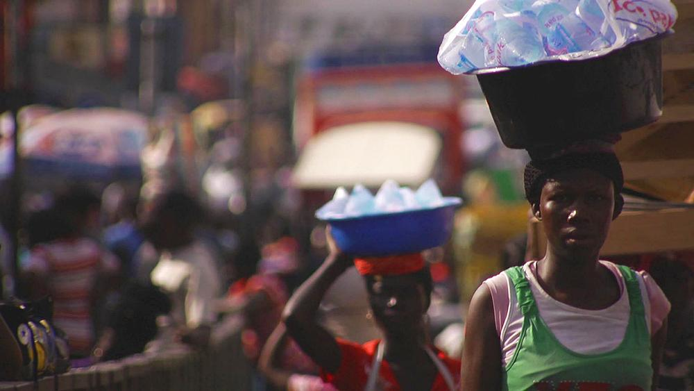 (slow motion) A woman carrying a bucket on her head with water bottles in it walking down a busy bustling street in Accra, Ghana, Africa