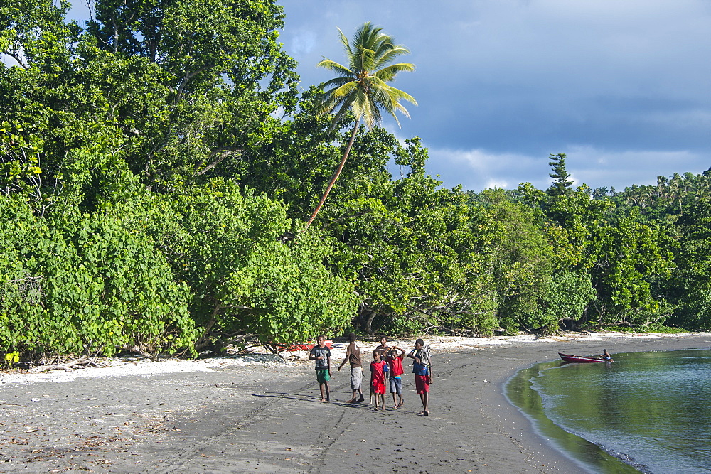 Local boys walking on a pretty black sand volcanic beach, Epi island, Shepherd islands, Vanuatu