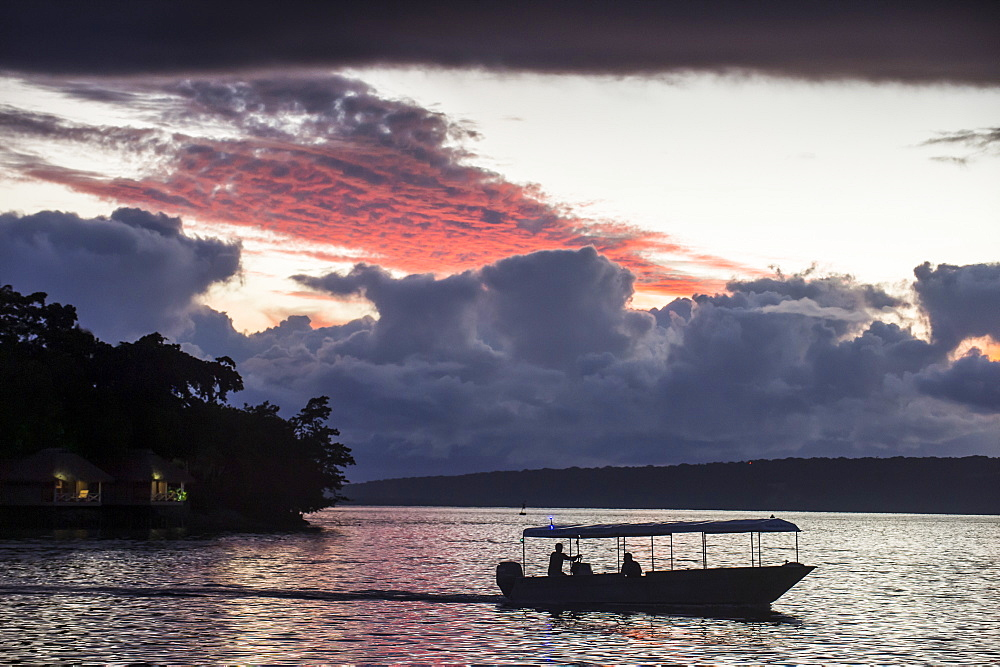 Tourist boat driving back home at sunset in Port Vila, Efate, Vanuatu