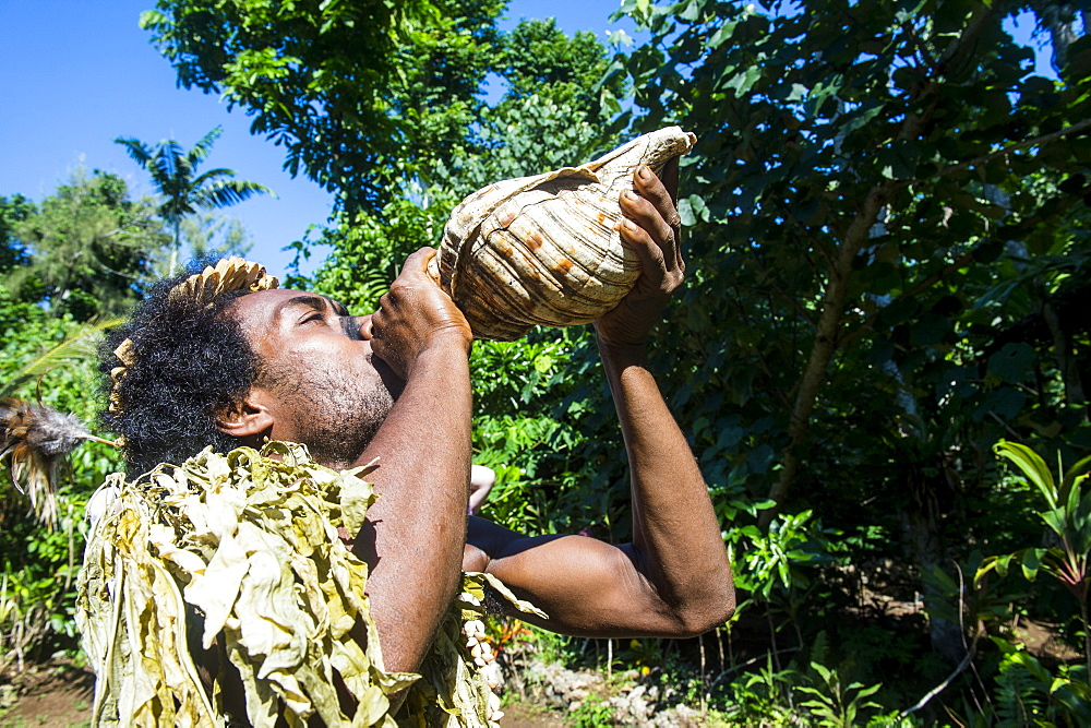 Man blowing in a giant shell, Ekasup Cultural Village, Efate, Vanuatu, Pacific