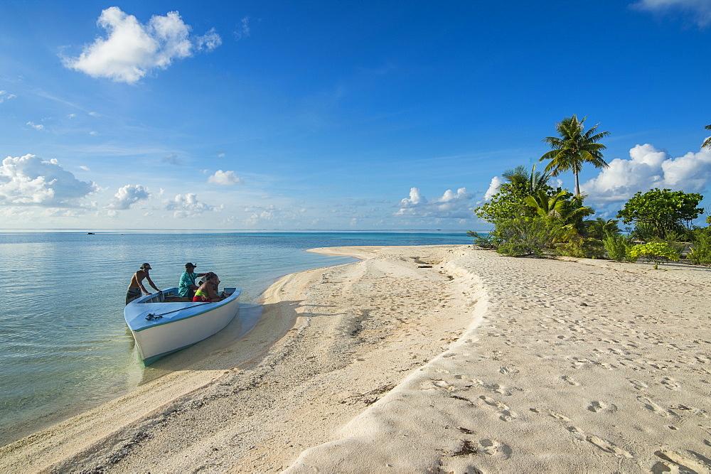 Beautiful palm fringed white sand beach in the turquoise waters of Tikehau, Tuamotus, French Polynesia
