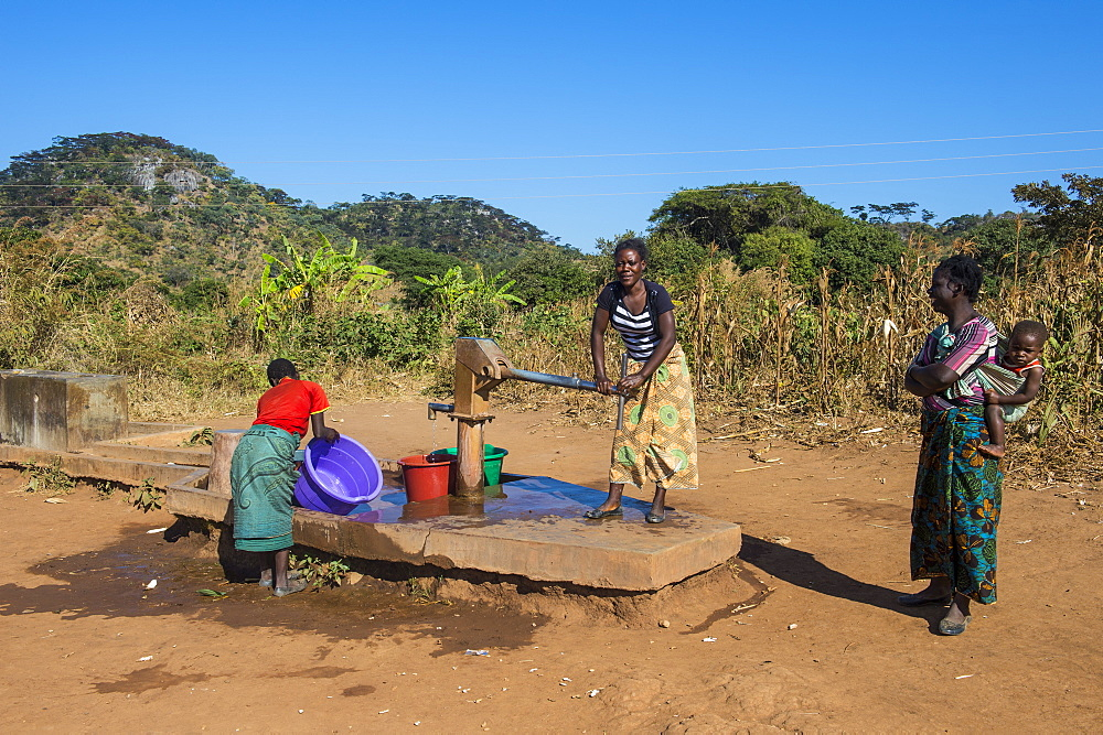 Local women on a water well, Malawi, Africa