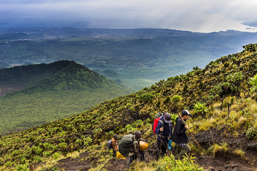 Trekkers on the steep slopes of Mount Nyiragongo, Virunga National Park, Democratic Republic of the Congo, Africa