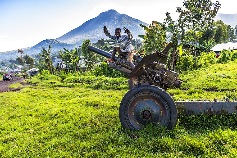 Boys posing on abandoned artillery in the Virunga National Park, Democratic Republic of the Congo, Africa