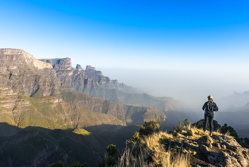 Woman enjoying the early morning sun on the cliffs, world heritage sight, Simien mountains national park, Debarq, Ethiopia - 1184-1762
