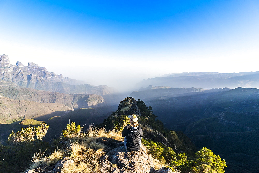 Woman enjoying the early morning sun on the cliffs, world heritage sight, Simien mountains national park, Debarq, Ethiopia - 1184-1764