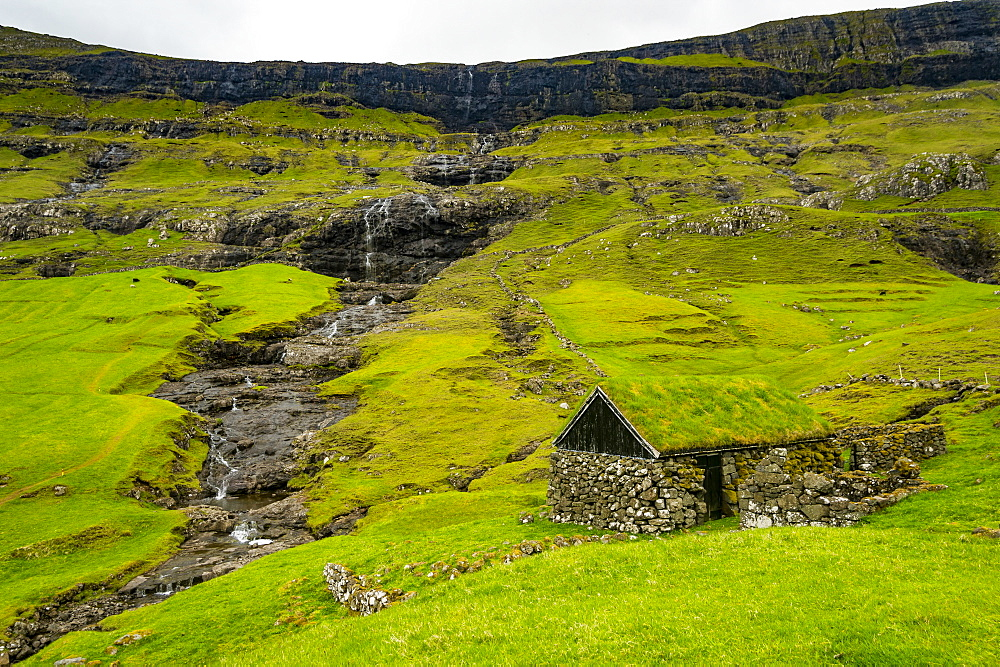 Grasstop roof house before a waterfall, Saksun, Streymoy, Faroe Islands, Denmark, Europe