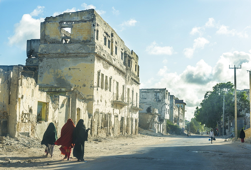 Somali women walking through the streets of the destroyed houses of Mogadishu, Somalia, Africa