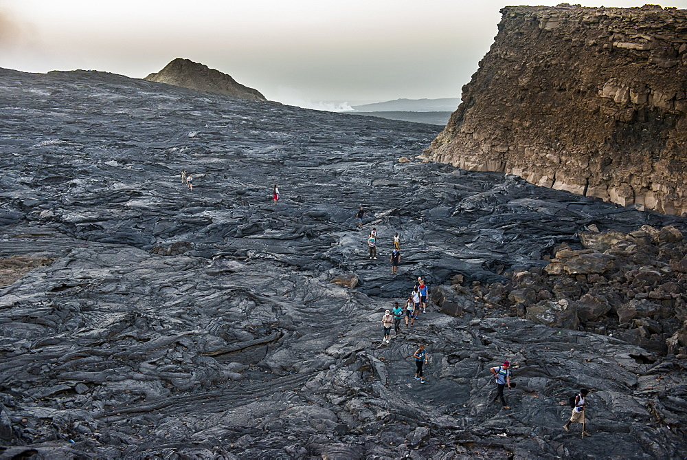 Tourists walking through a lava field on Erta Ale