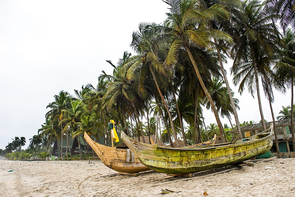 Fishing boats on a palm fringed beach in Assinie, Ivory coast