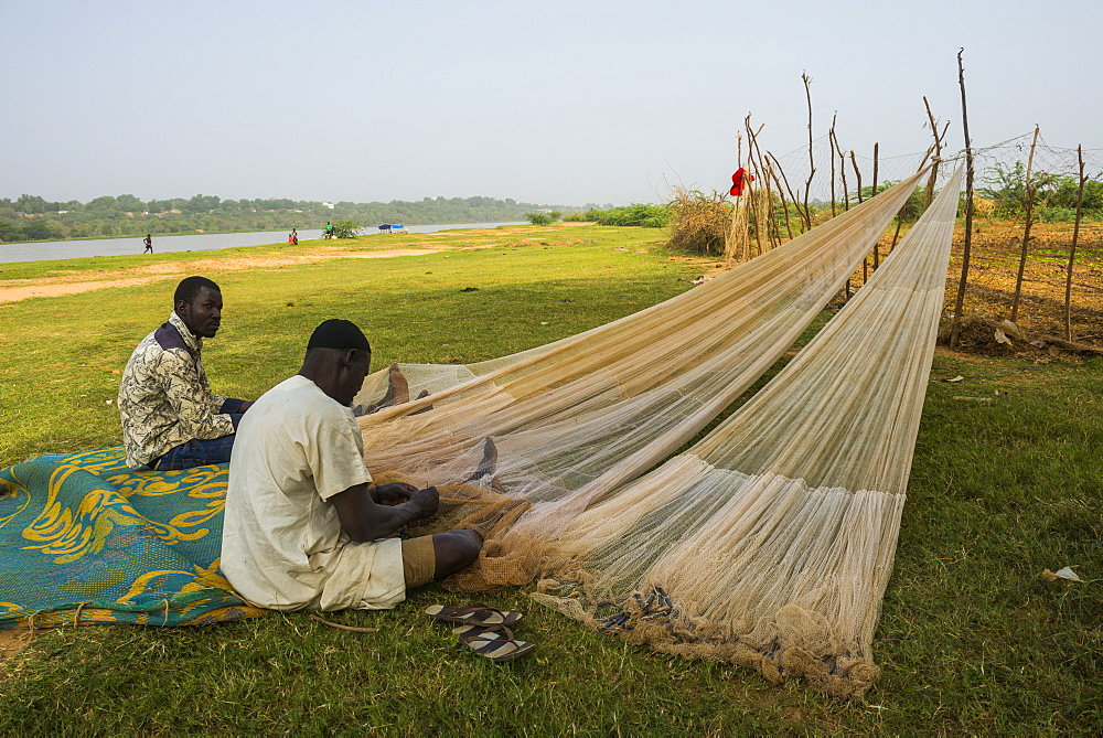Fishermen repairing their fishing nets on the River Niger, Niamey, Niger, Africa