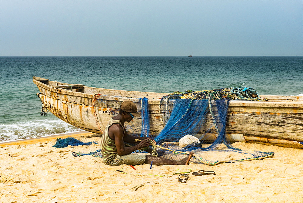 Man fixing their nets in their fishing boats on a beach in Robertsport, Liberia