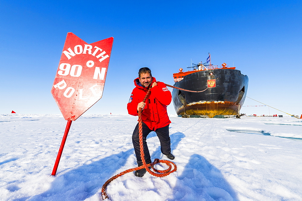 Man pretending to pull the Icebreaker '50 years of victory' on the North Pole, Arctic