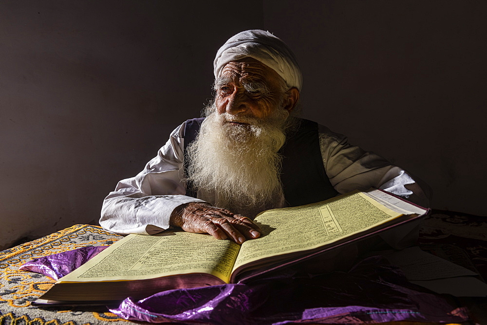 Sufi priest studying the holy Quran in the Shrine of Mawlana Abdur Rahman Jami, Herat's greatest 15th century poet, Herat, Afghanistan, Asia