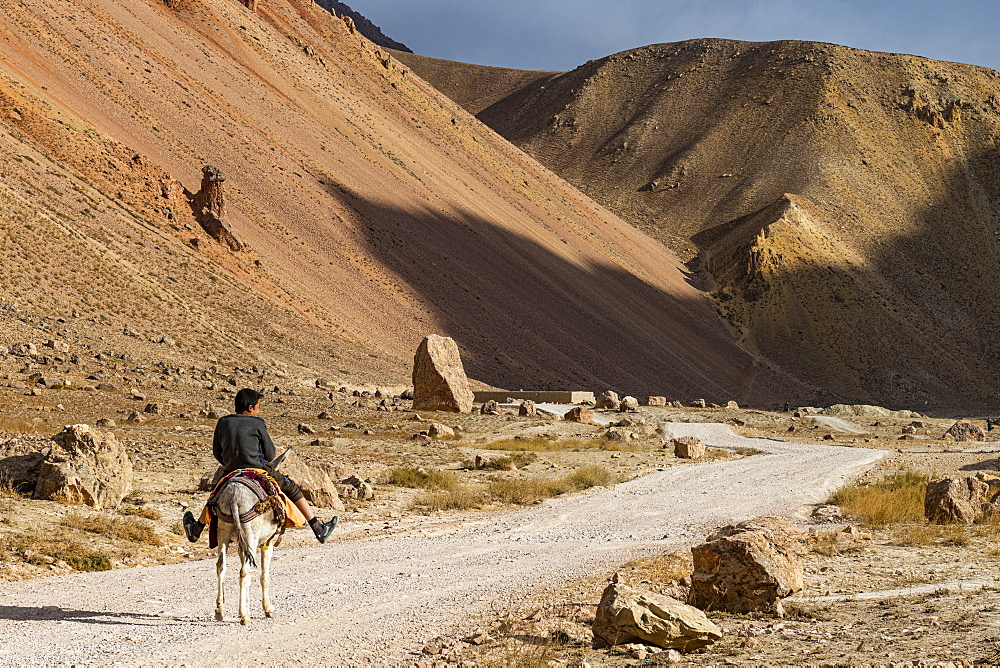 Man with his horse in the valley of Chehel Burj or forty towers fortress, Yaklawang province, Bamyan, Afghanistan