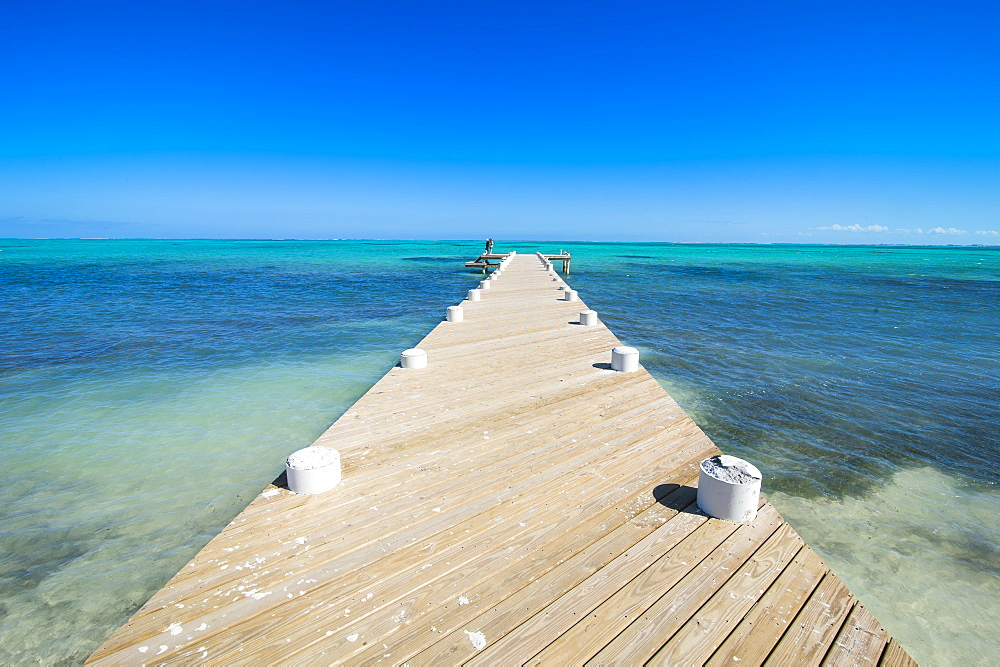 Long wooden pier in the turquoise waters of Providenciales, Turks and Caicos, Caribbean, Central America