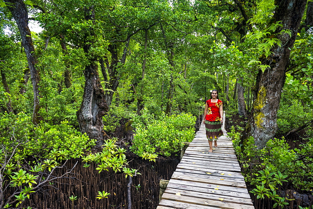 Local girl walking along a long wooden pier, Kosrae, Federated States of Micronesia, South Pacific