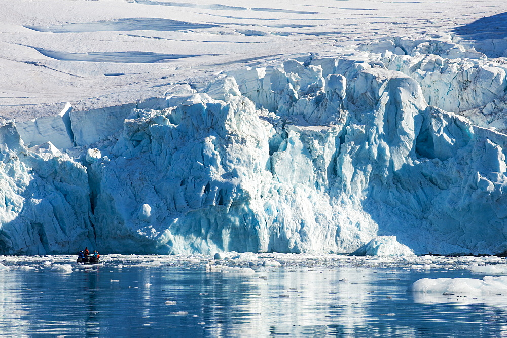 Zodiac with tourists cruising in front of a huge glacier, Hope Bay, Antarctica, Polar Regions