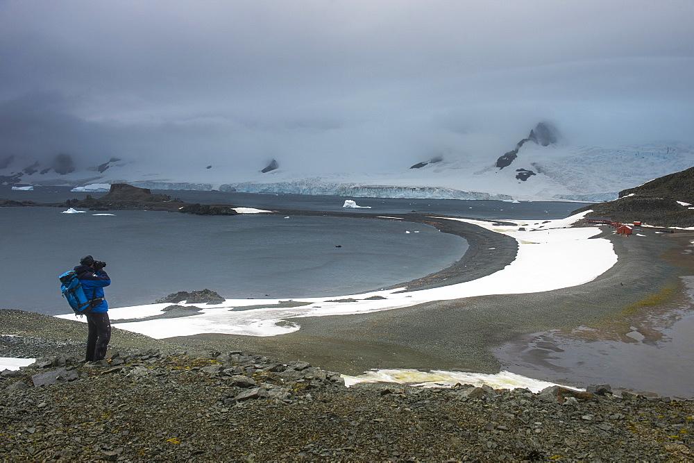 Tourist photographing from an overlook over Half Moon Island, South Shetland Islands, Antarctica, Polar Regions