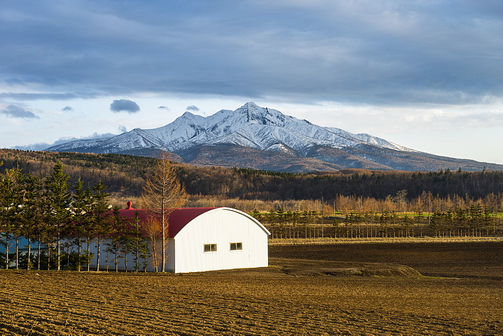 Little farm before a snow capped mountain near the Shiretoko National Park, Hokkaido, Japan, Asia