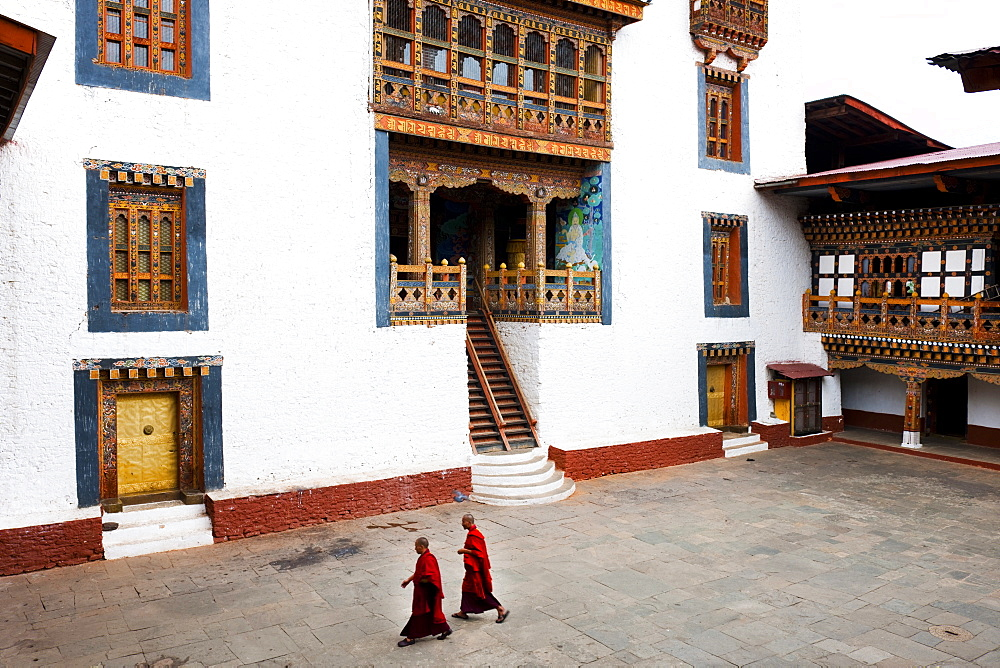 Monks walking through the courtyard of Punakha Dzong, Punakha District, Bhutan, Asia