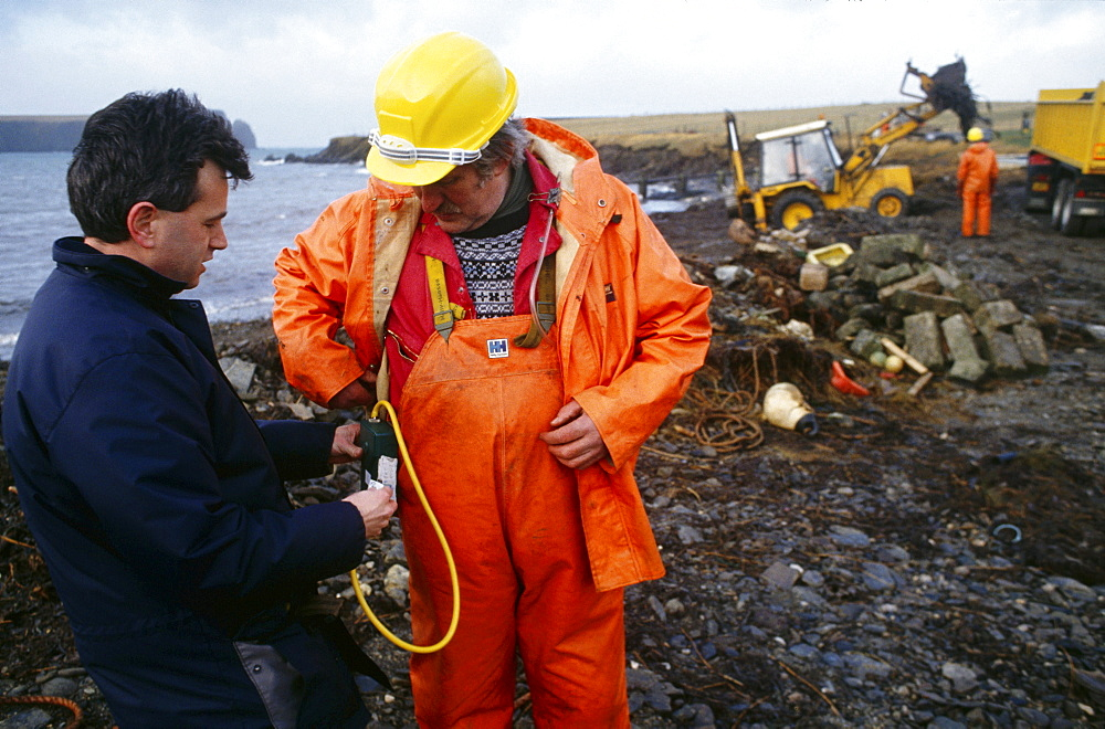 Shetland islands, oil disaster. Scientist from b.p. Group occupational health centre conducting air tests on council workmen cleaning up the oil. On 5th january 1993, the oil tanker the braer ran aground in the shetland islands spilling 85,000 tonnes of light crude oil