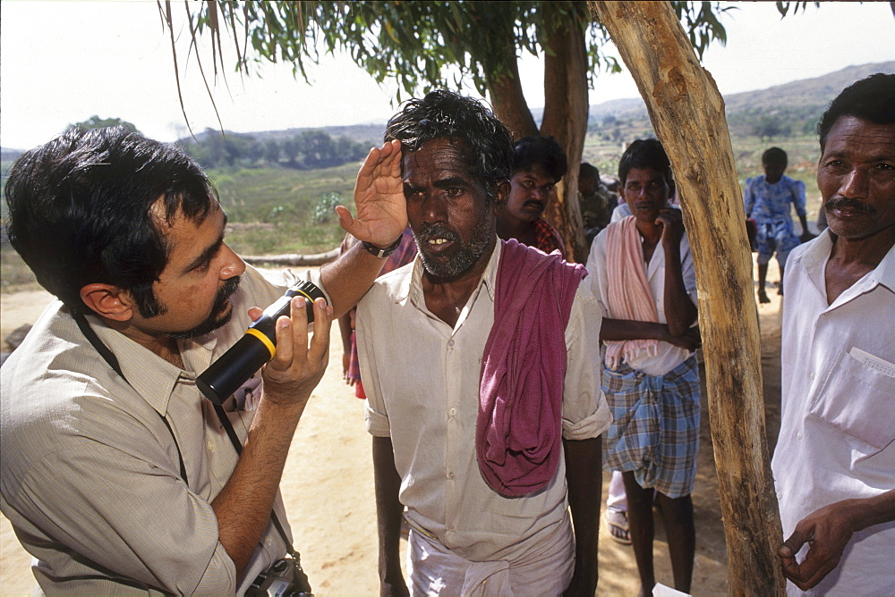 Health, india. Andhra pradesh, rishi valley. Centre for new education. Doctor examining mans eyes for cataracts.