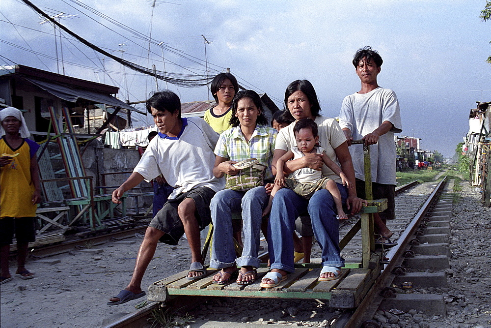 Transport, philippines. Manila. Sucat railway community. Human powered railway taxi. Young men ferry passengers along the track in makeshift wagons. When trains come they lift the wagons off the track, wait until the coast is clear and resume their journey. Over 10,000 families live along this railway track. there are plans to upgrade the line which would mean the community would have to re-locate