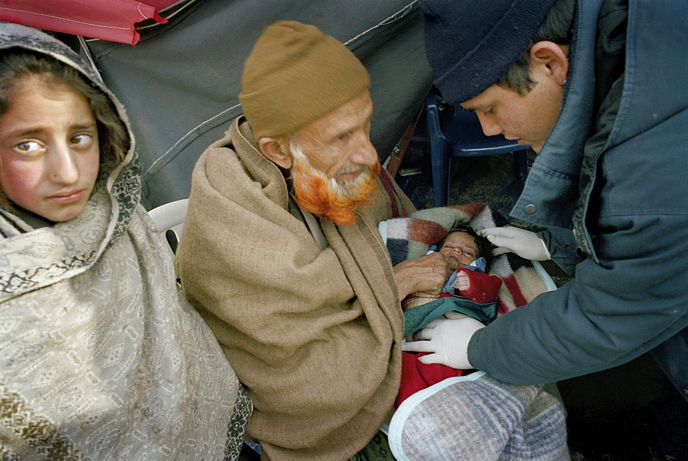 Earthquake aftermath, pakistan. Alaai. Cuban doctors sent by fidel castro have set up field hospitals in the earthquake zone complete with operating theatres. Baby suffering from dysentery receives emergency treatment.