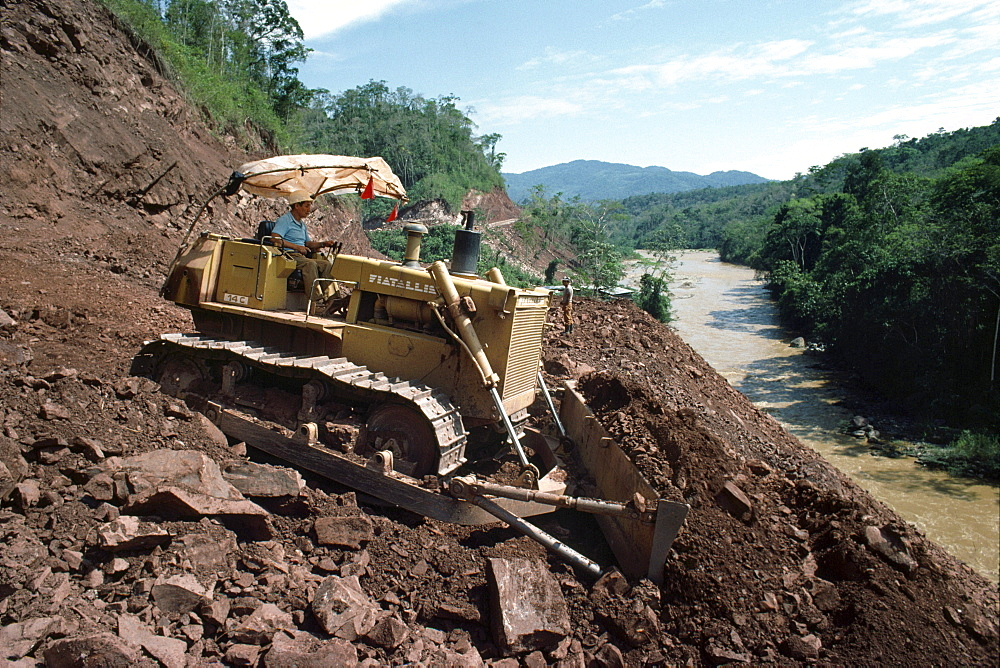 Amazon, peru. Satipo, puerto prado road. A bulldozer scraping the bed of an east-west running road connecting satipo to puerto prado on the humid, eastern side of the peruvian andes east of lima. Roads, whether for transport or logging, serve to open up the rainforest to settlers