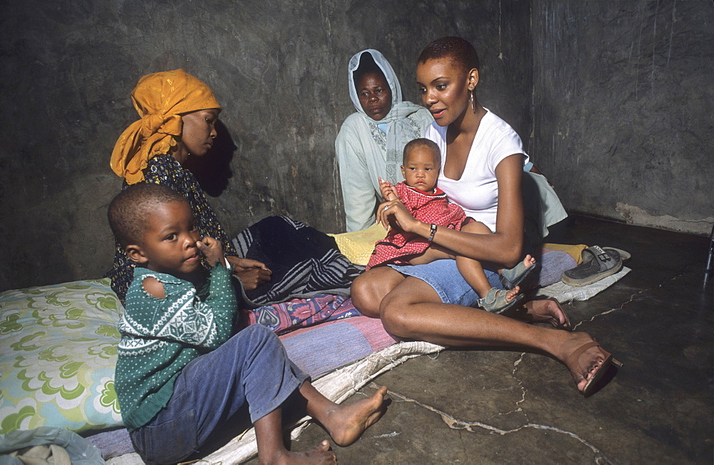 Aids patient, botswana. Gabane village, near gaberone. Mpule kwelagobe, miss universe 1999 with dipuo & her children. A third of botswanas sexually active population is hiv-positive