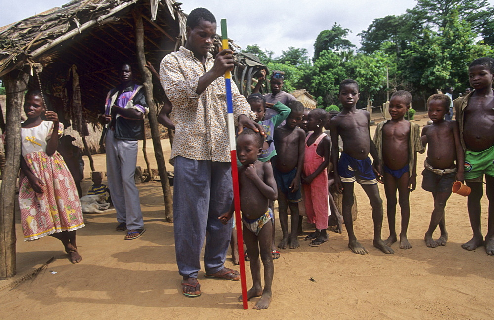Onchoceriasis, ivory coast. Bouake. Who river blindness prevention, measuring children to determine correct dose for ivermectin tablets. The dots on the pole indicates correct dose.