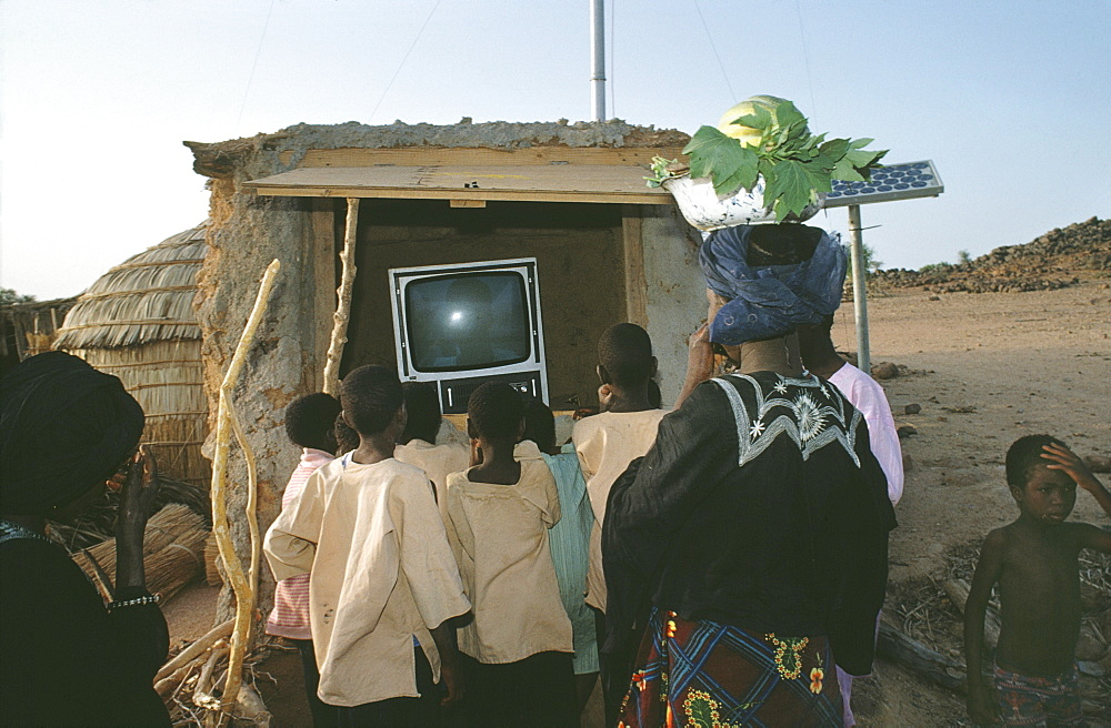 Solar-powered tv, niger (west africa). Tahoua village. Tv run on a battery charged by solar panels. For the first time, a view of the world is seen by the villagers