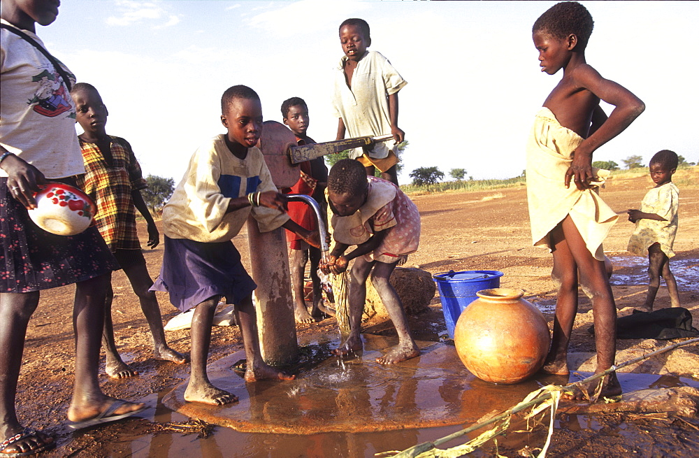 Collecting water, burkina faso. Silmiougou village. Children draw water from the village pump