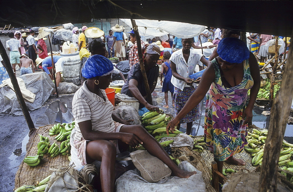 Slums, haiti. Cite soleil shanty town. Port, au, prince. Buying vegetables in a street market. These are among the most disadvantaged people in the world.