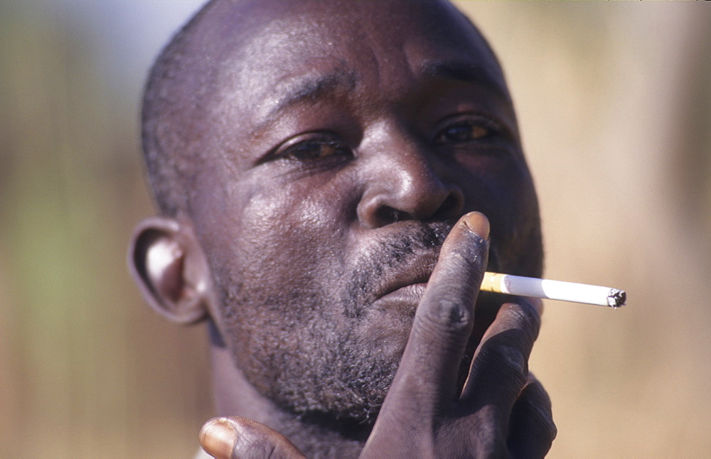 Man smoking, burkina faso. Silmiougou village. Cigarette