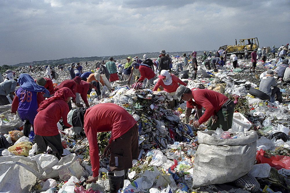 Recycling, philippines. Manila. Scavengers sorting through rubbish at payatas landfill site. They sell to dealers who re-sell glass, plastic, paper, etc to manufacturers who produce new products from waste