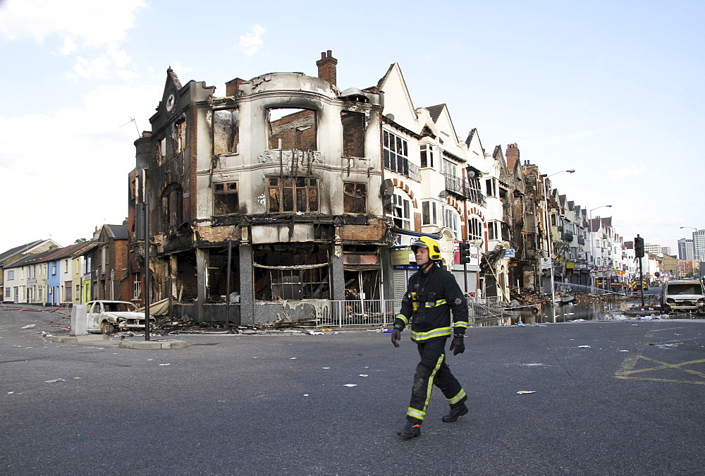 Firefiighter inspects damage to property after riots and looting in Croydon, London, UK ;