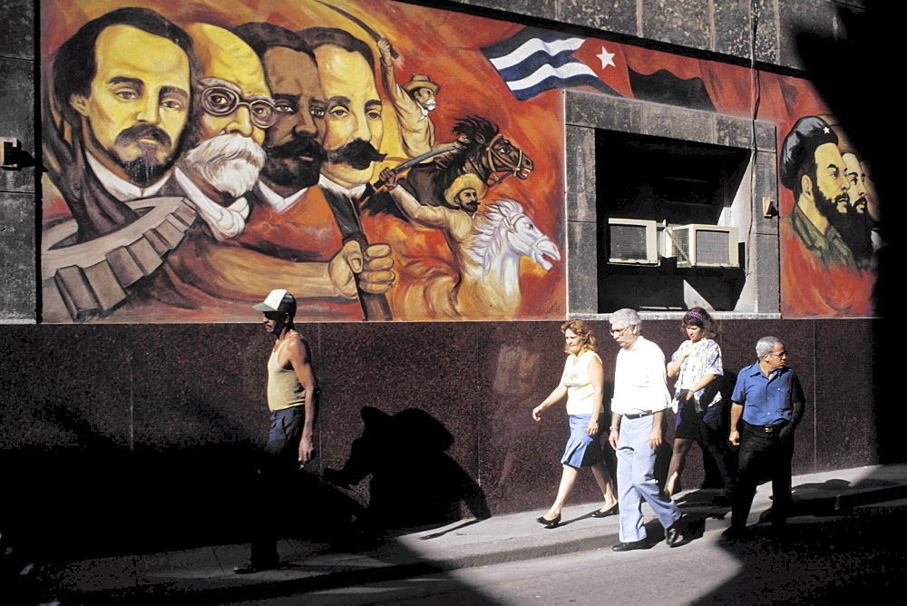 Mural, cuba. Havana. Pedestrians walking past a wall painting in the old part of havana
