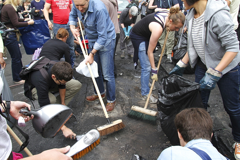 Local community get together to clear damage caused by rioters in Hackney, London, UK ;