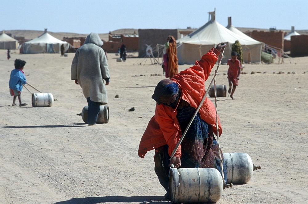 Western sahara. Women and children carrying gas bottles. Polisario smara camp.
