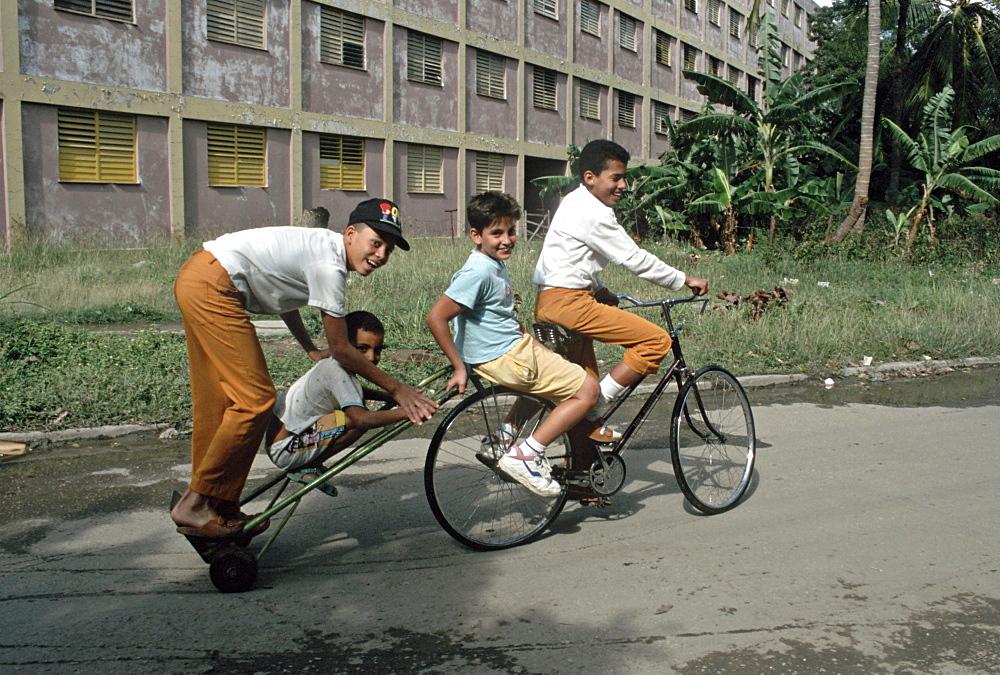 Cuba children on a long bycicle havana