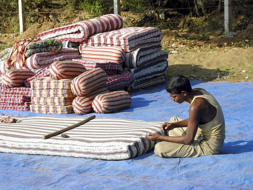 India. Fixing matresses in the streets of mumbai.