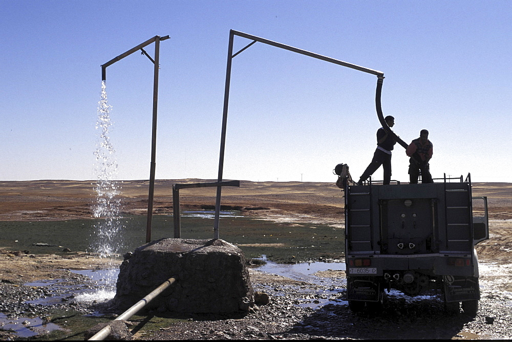 Refugee camp, algeria. Lorries loading water from main pipe at polisario central camp