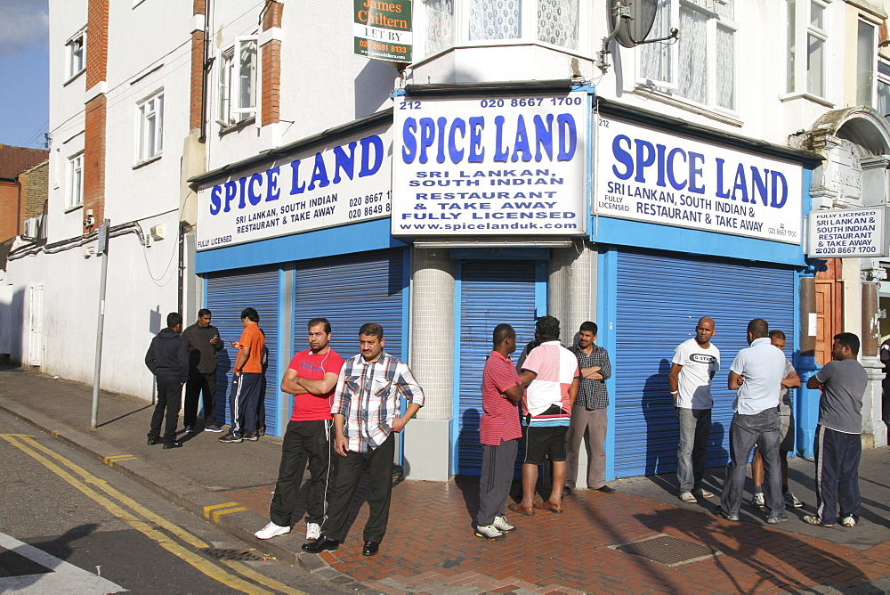 Local residents watch damage to property after riots and looting in Croydon, London, UK ;