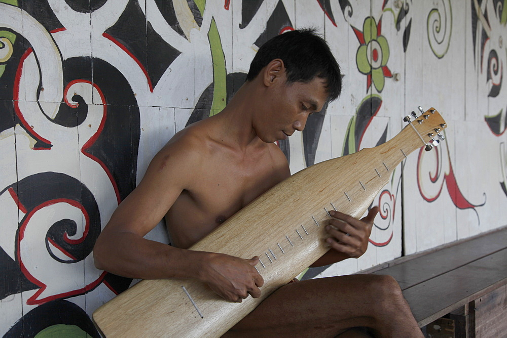 Iban man playing traditional instrument in a native Iban longhouse in Borneo, Malaysia